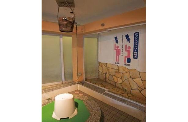 天然温泉 湘南ひらつか 太古の湯の「バケツシャワー」。その名のごとく、ひもを引いて天井のバケツの水をザバーッと浴びる。まるでコント!