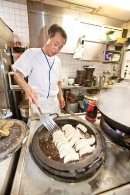 丸い鉄鍋で焼くスタイルの「つけ麺 江戸一」(川崎駅東口)の「焼餃子」(6個470円)