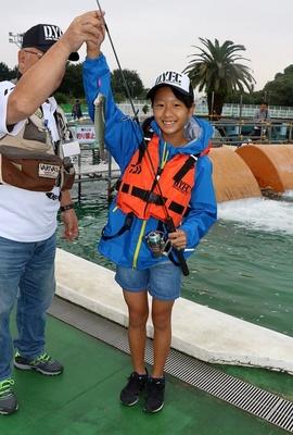 東京都としまえんフィッシングエリアでベースキャンプトラウトスクールが開催。ニジマスを釣り上げ笑顔を見せる女の子