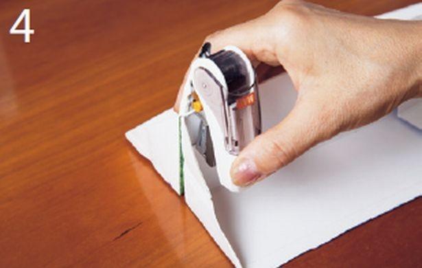 内側が表になるようにパックを開 いて山形になるように折り、底側 の端をホチキスで留める。同じも のをもう1つ作る