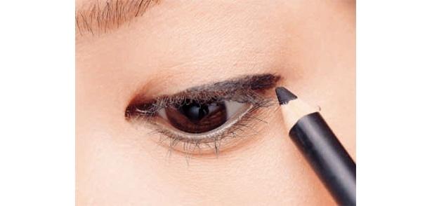 黒のペンシルで上のアイラインを目頭側から引いていきます。「黒目の内側からやや太めに描き、目尻にかけてかなり太くしましょう。長さは自分の目尻より少し外側まで」