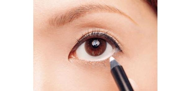 白いペンシルで目の下のキワぎりぎりにラインを引きます。「まつ毛の生えギワより内側の、赤い粘膜のところを埋めるようにして引くのがポイント。