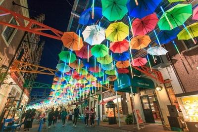 頭上を彩るたくさんのカラフルな傘。夜には音楽に合わせて降り注ぐ光と3Dイルミネーションで賑やかな雰囲気へと様変わりする