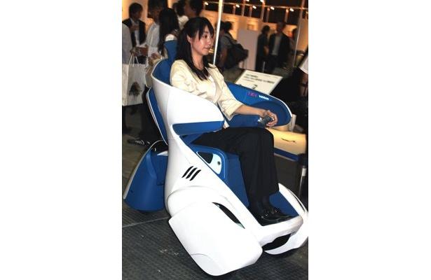 """トヨタ自動車の小型3輪自動車「i-REAL」は、車輪が3つ付いた""""ソファ""""。座りながら手元の操作だけで、""""運転""""ができるという、マンガや映画に出てきそうな乗り物だ"""