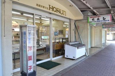 目の前の道路を境に東京都清瀬市と埼玉県新座市に分かれ、「ホルン洋菓子店」は埼玉県側。道路の向かいには旭が丘団地が並ぶ