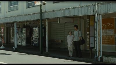 「団地センター」のバス停で清瀬駅行きのバスを待つ良多と見送りに来た母