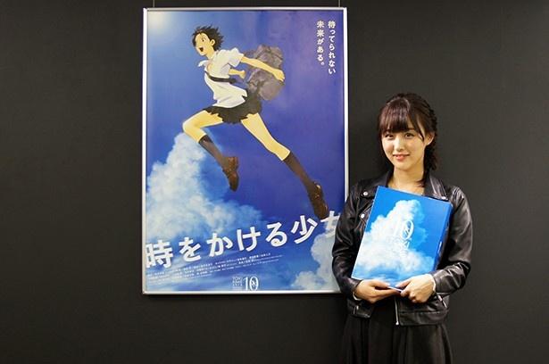 ポスターを背景に記念BOXを抱えて写真に収まる鎌田菜月さん
