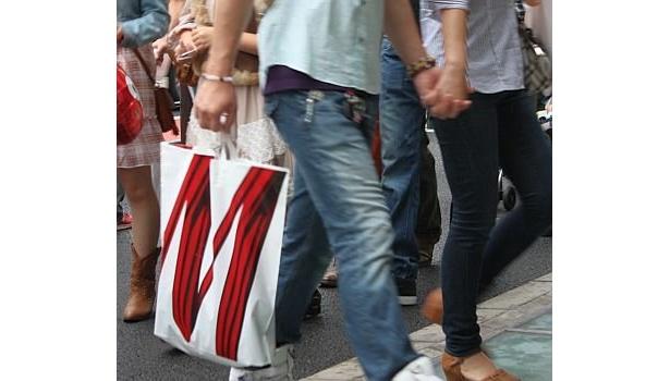H&Mのショッピングバッグを持って歩く人