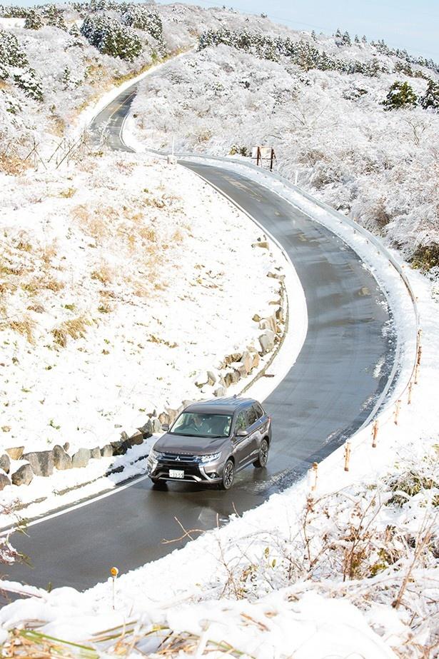 冬の山道を走るアウトランダーPHEV