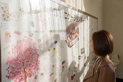 食堂の壁に設けられたコミュニケーションボードに書かれたメッセージを読む水村リア