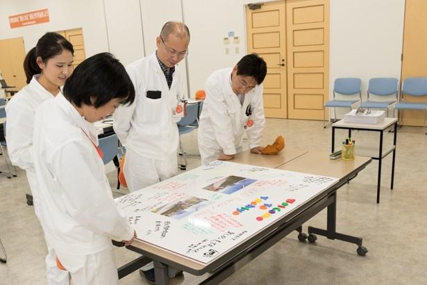 参加者が去った後、書き記されたメッセージを読む工場の方々