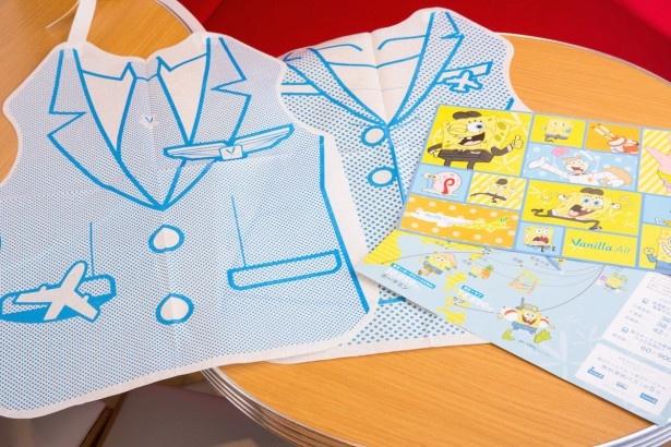 キャラクターや成田国際空港までのアクセスを描いたランチョンシート&パイロットとフライトアテンダント風の紙エプロン。2種類のうちどちらをもらえるかはお楽しみ