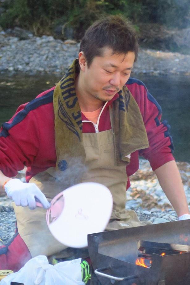 慣れた手つきでホタテを焼く新井