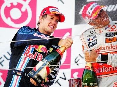 レース後、ポディウム(表彰台)でシャンパンファイトをするベッテル選手。右は3位のルイス・ハミルトン選手