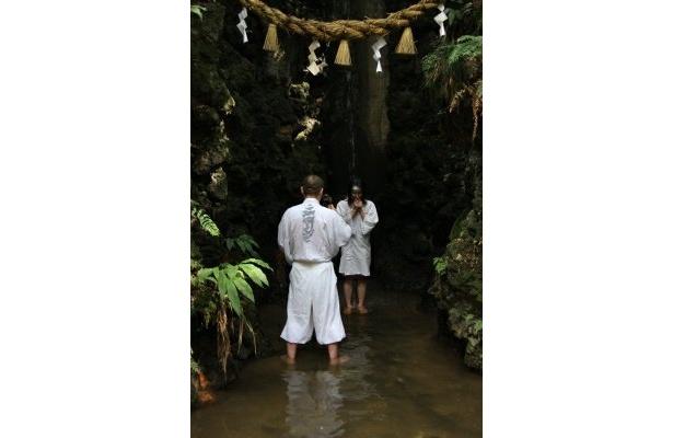 こんな貴重な体験も!滝行は、水着の上に白衣を羽織ってトライ