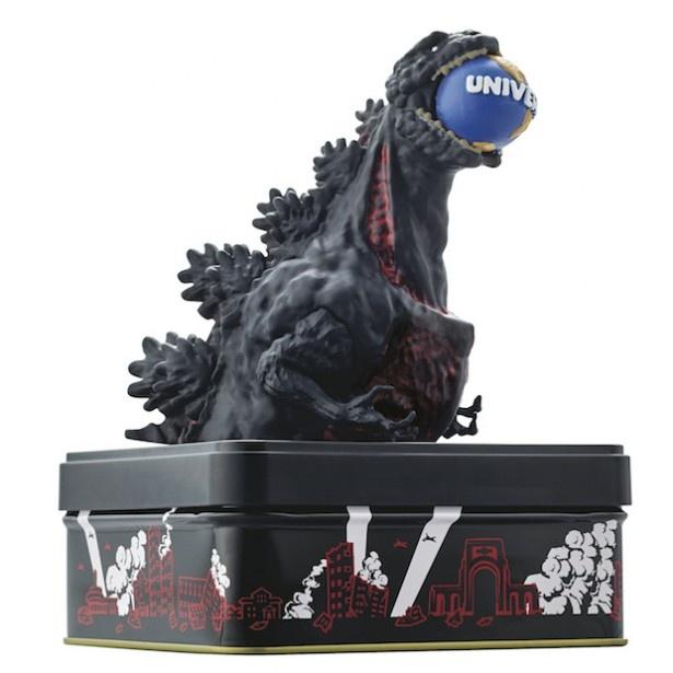 ユニバーサル・グローブを口にくわえているゴジラをテーマにした「フィギュア缶入りスナック」(画像提供:ユニバーサル・スタジオ・ジャパン)