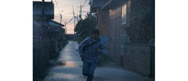土砂降りの中、新聞配達を続ける和也